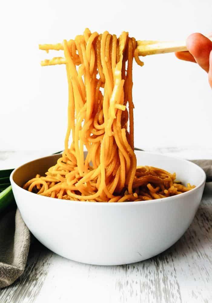 hand holding chop sticks picking up fried noodles