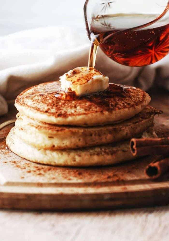 stack of fluffy buttermilk pancakes with butter and syrup