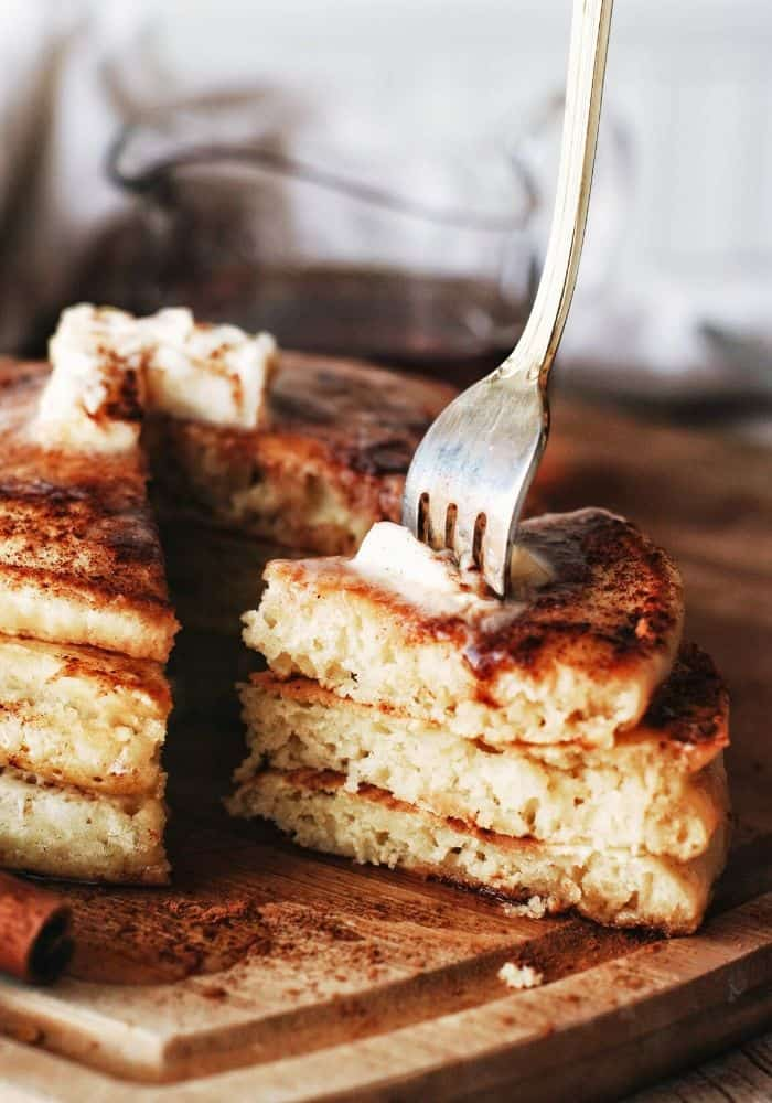 stack of pancakes with cinnamon sticks and a fork taking a slice out