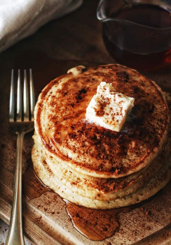 overhead shot of pancakes with cinnamon and butter and syrup