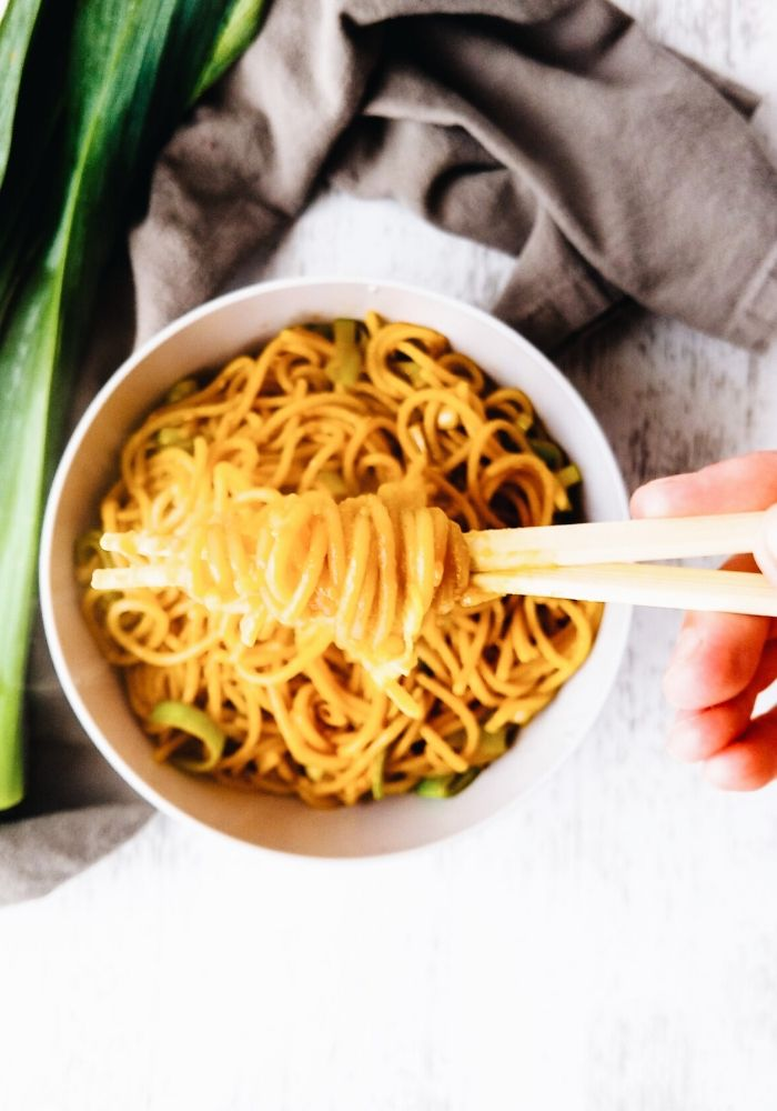 hand lifting up stir fried noodles