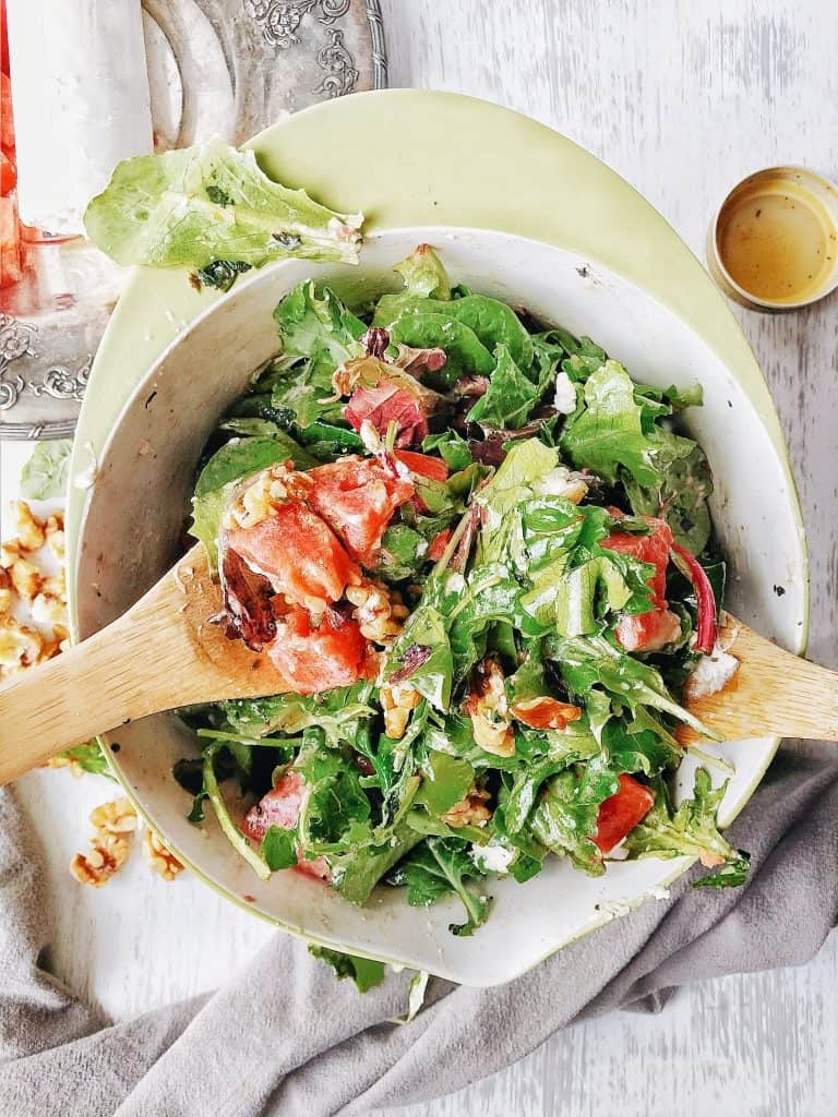 watermelon salad with spring mix and goat cheese being tossed