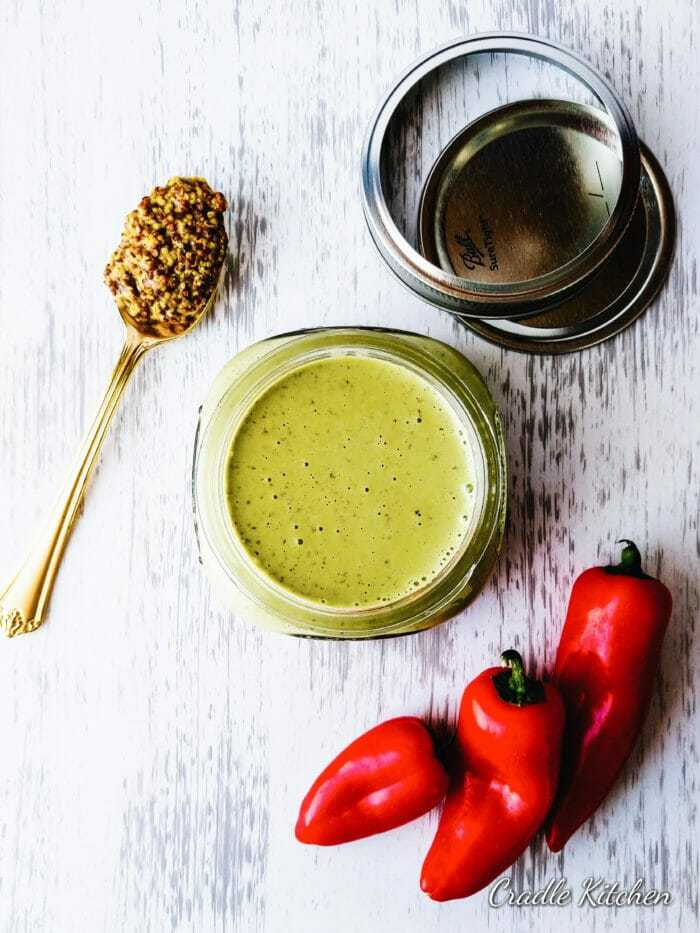 jar of cilantro sauce next to red peppers and whole grain mustard