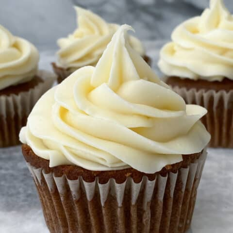 Carrot Cake Cupcake with cream cheese frosting on a marble counter top