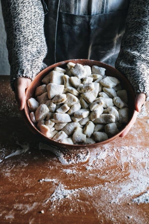 hands holding a bowl of fresh made gnocchi