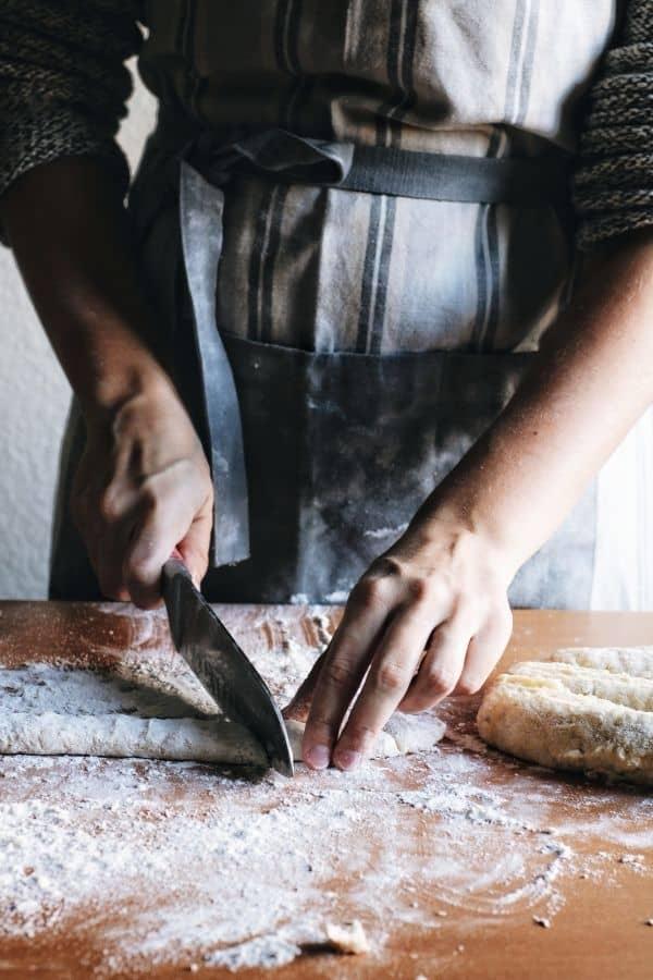 hands cutting gnocchi dough into pieces