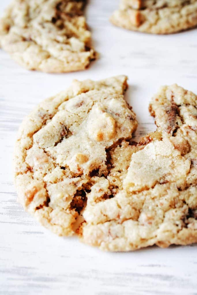a cookie with heath bar bits broken open to see gooey center