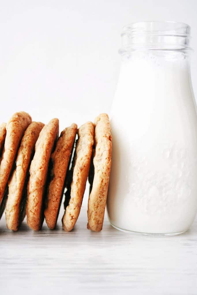 vertical stacked heath bar cookies next to glass of milk