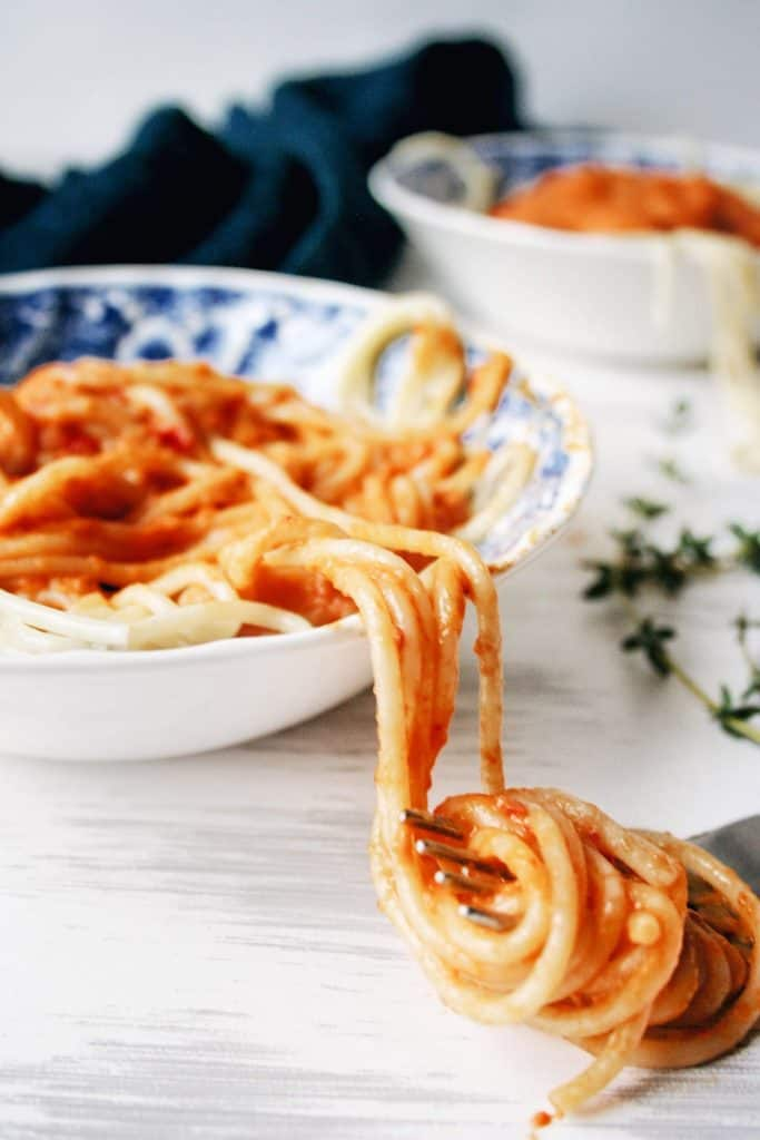 a twirl of pasta with red pepper sauce on a fork