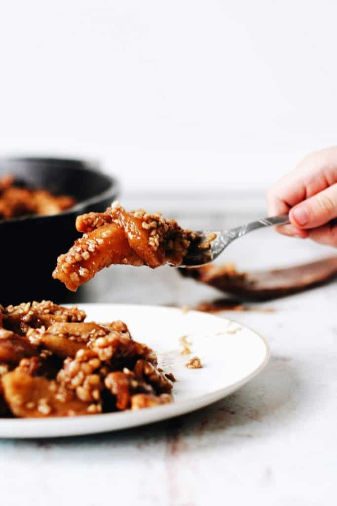 hand eating apple crumble on a fork