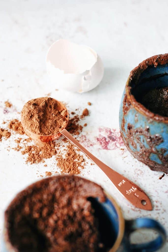 2 blue mugs of chocolate mug cake with a tablespoon of unsweetened cocoa powder