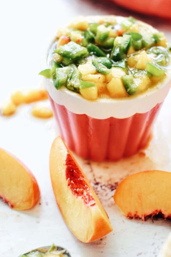 close up of peach and jalapeno salsa with fresh peach slices