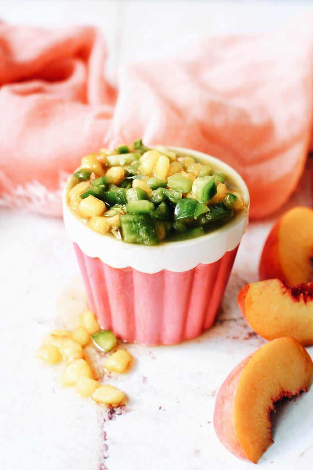 jalapeno and peach salsa in a cute pink cup with peach slices around it