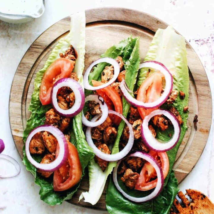a platter of lettuce holding chicken gyros