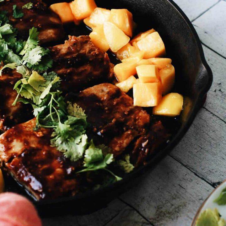 mahi mahi in a cast iron skillet with mango chunks and cilantro