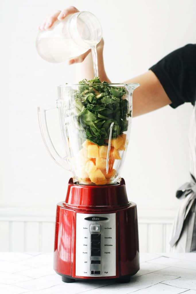 hand pouring aloe juice into a blender for a green smoothie recipe