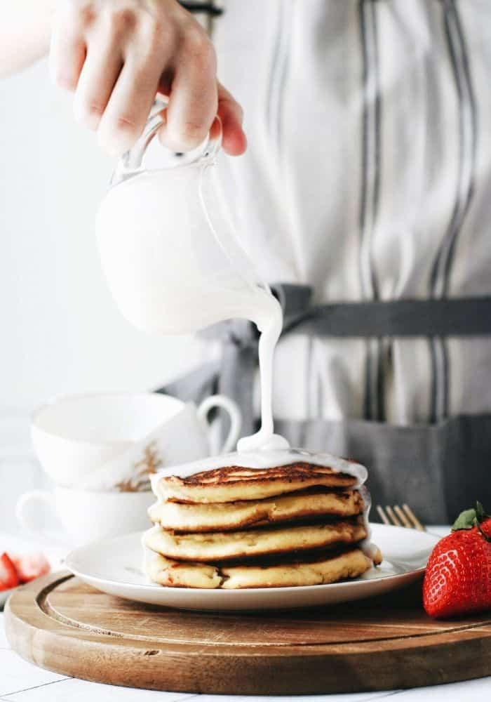 hand pouring icing over strawberry almond flour pancakes