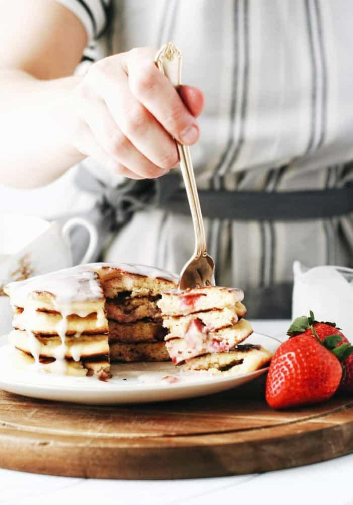 hand about to take a bite of pancakes with strawberries
