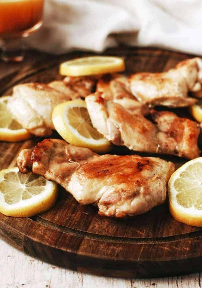 a wooden platter of chicken thighs with lemon and honey mustard sauce