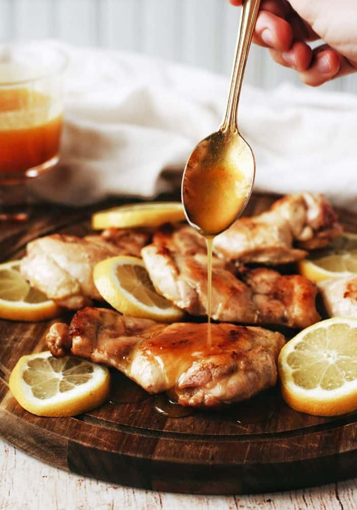 hand drizzling honey mustard over the chicken thighs