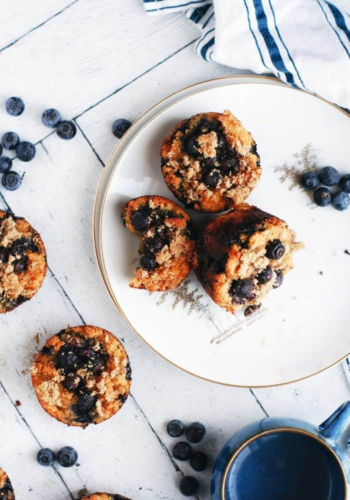 overhead shot of blueberry sweet potato muffins on a plate and blueberries scattered