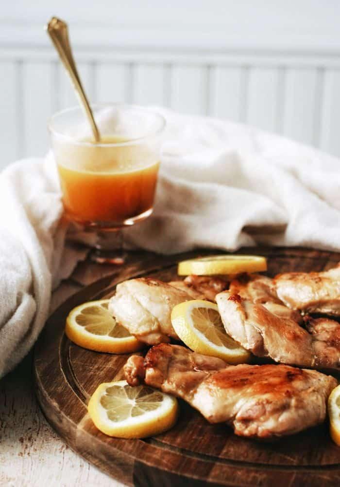 platter of chicken thighs with a glass of homemade honey mustard sauce