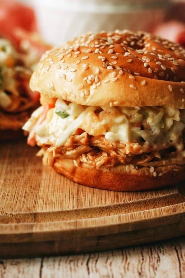 close up of a sesame seed bun with pulled chicken and coleslaw