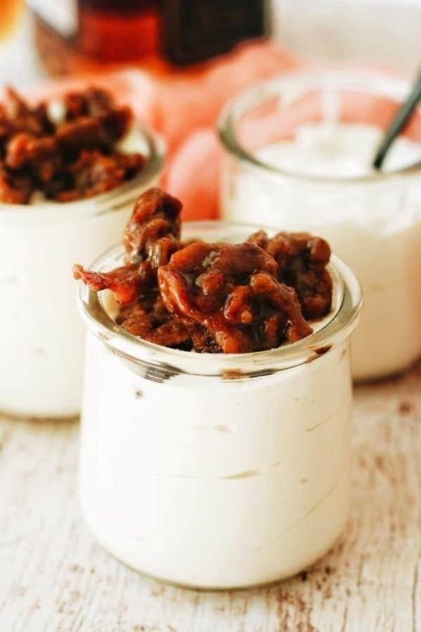 jars of no bake cheesecake with candied bacon on top