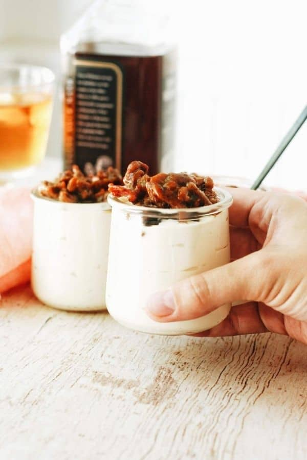 hand grabbing some cheesecake in a jar with candy bacon