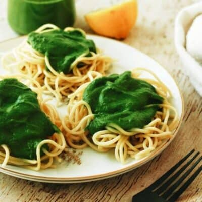 plate full of spaghetti and spinach pesto