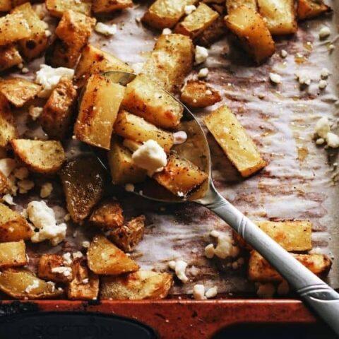 overhead shot of a spoon scooping up crispy roast potatoes on a baking sheet