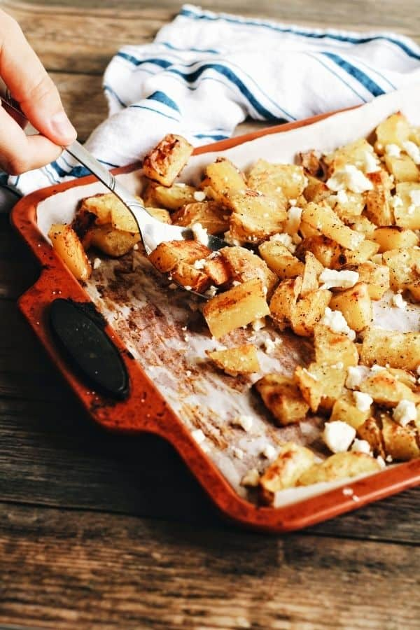 hand scooping up some garlicky roast potatoes with feta of a baking sheet