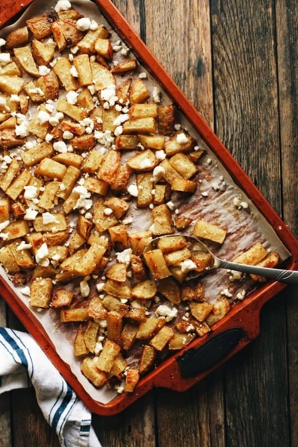 full overhead shot of a pan full of oven roasted garlicky potatoes and feta