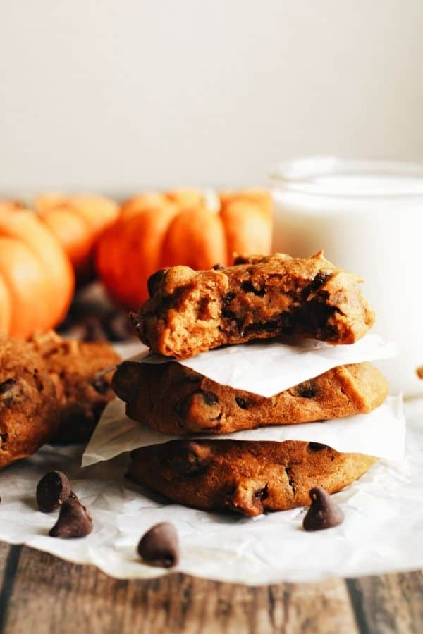 a stack of pumpkin chocolate chip cookies with pumpkins in the background