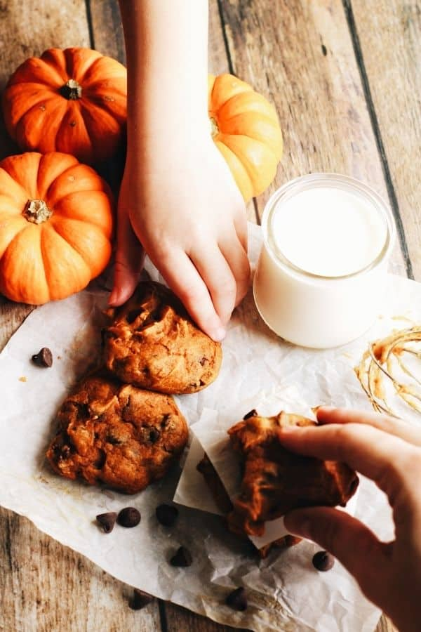hands grabbing for some pumpkin chocolate chip cookies with pumpkins