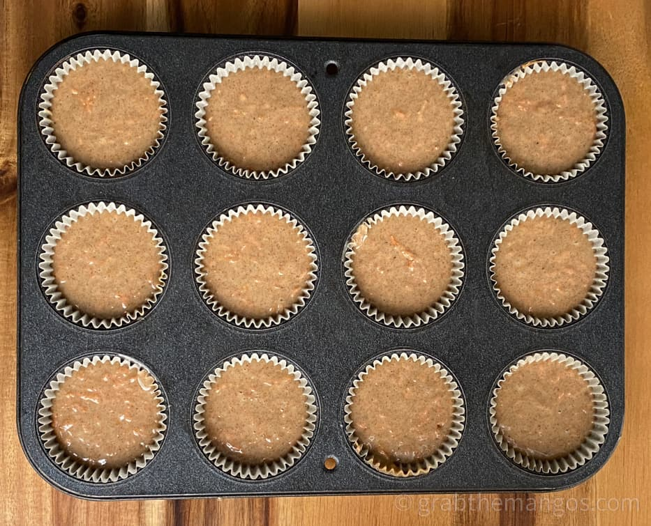 carrot cake cupcakes in a muffin tin with muffin tin liners on a cutting board