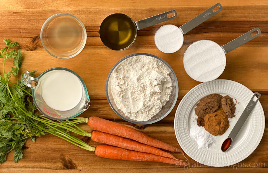 ingredients for carrot cake on a cutting board. Carrots, milk, flour, spices, sugar, baking soda, olive oil, and apple cider vinegar.