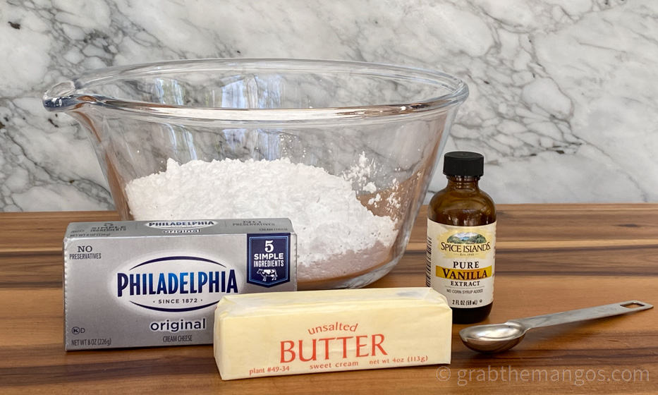 ingredients for frosting. Sugar in a glass bowl, a package of Philadelphia cream cheese, unwrapped butter, vanilla. and a teaspoon on a cutting board