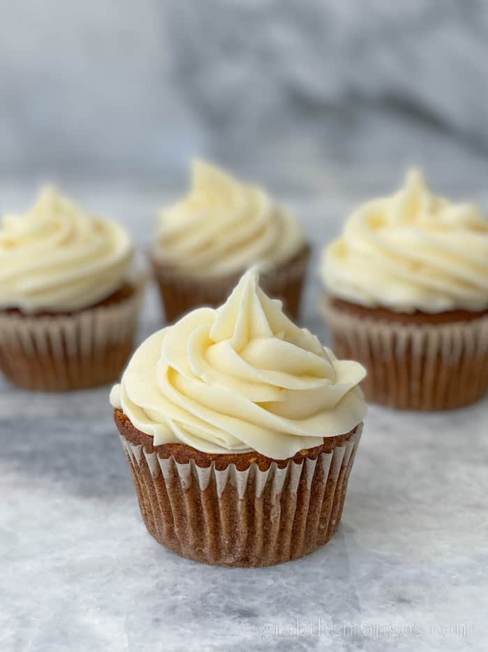 carrot cake cupcakes with cream cheese frosting on a marble counter top