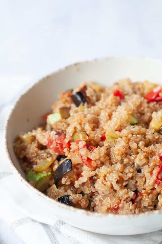 close up photo of quinoa in a white bowl with cooked vegetables.