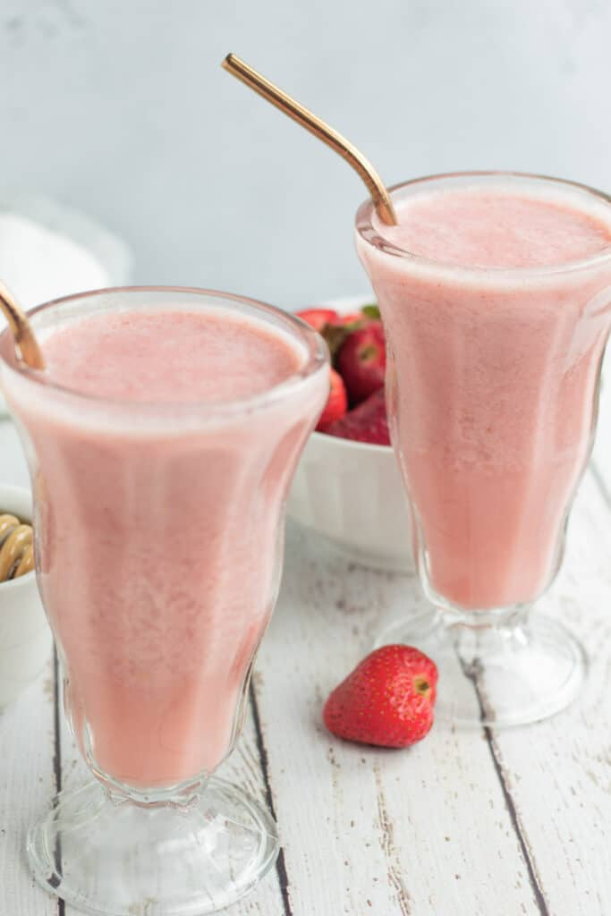 close up of two strawberry smoothies in glass with strawberries on table