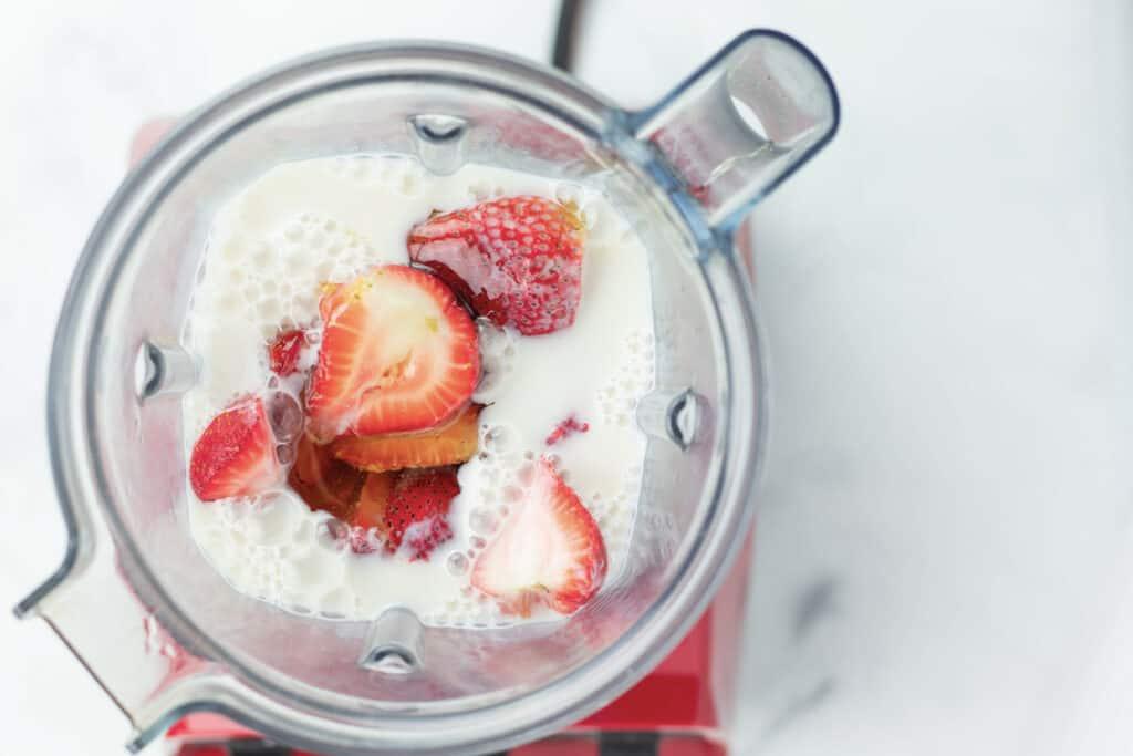 sliced strawberries in a blender with milk not yet blended