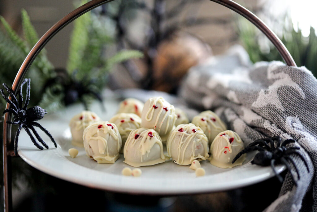 white chocolate mummy truffles on a plate with fake spiders