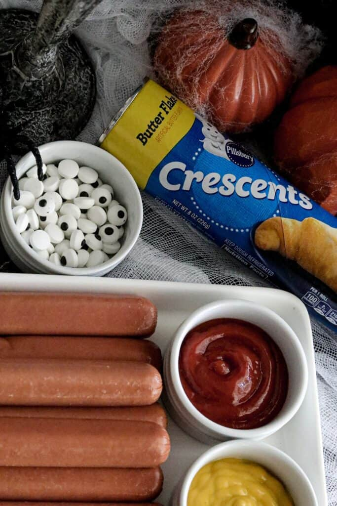 Plate with raw hotdogs, and bowls of ketchup and mustard with a bowl to the top left of candy eyes and a can of crescents on the top right
