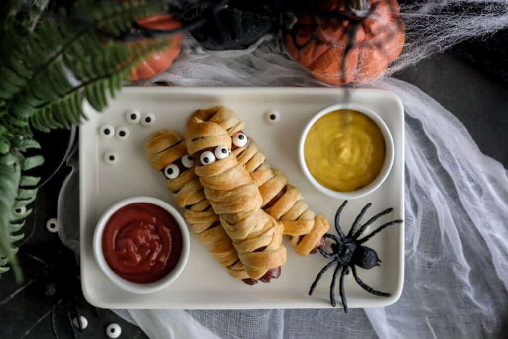 crescent roll mummy hotdogs on a white plate with ketchup and mustard on either side with spiders