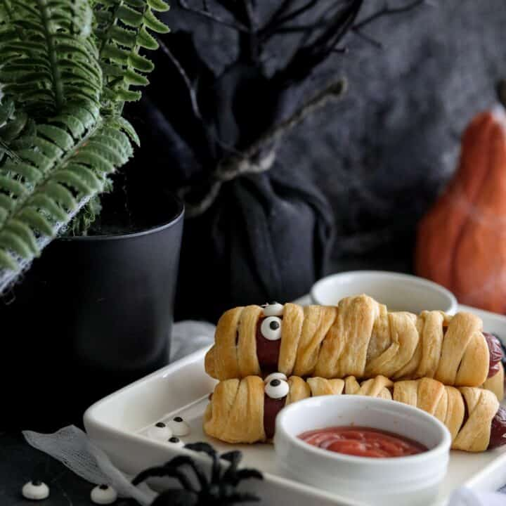 Halloween Mummy Hotdogs on a plate with a bowl of ketchup
