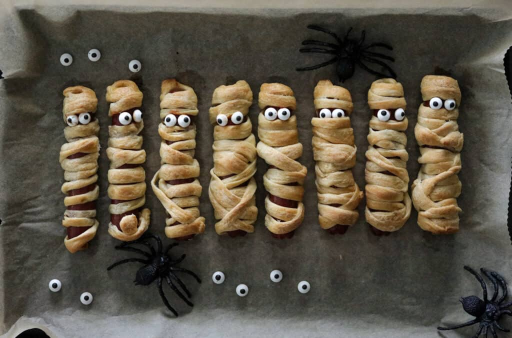 cooked mummy dogs with candy googly eyes on a parchment lined baking sheet with google eyes and spiders around it.