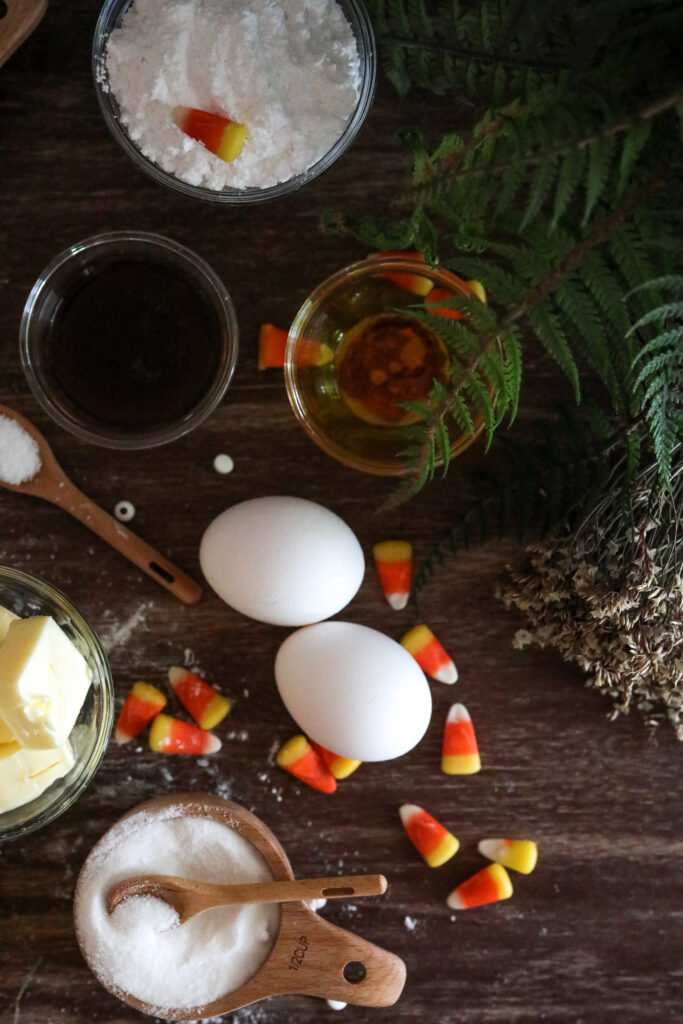 ingredients for Halloween cupcakes including eggs  on a wood cutting board