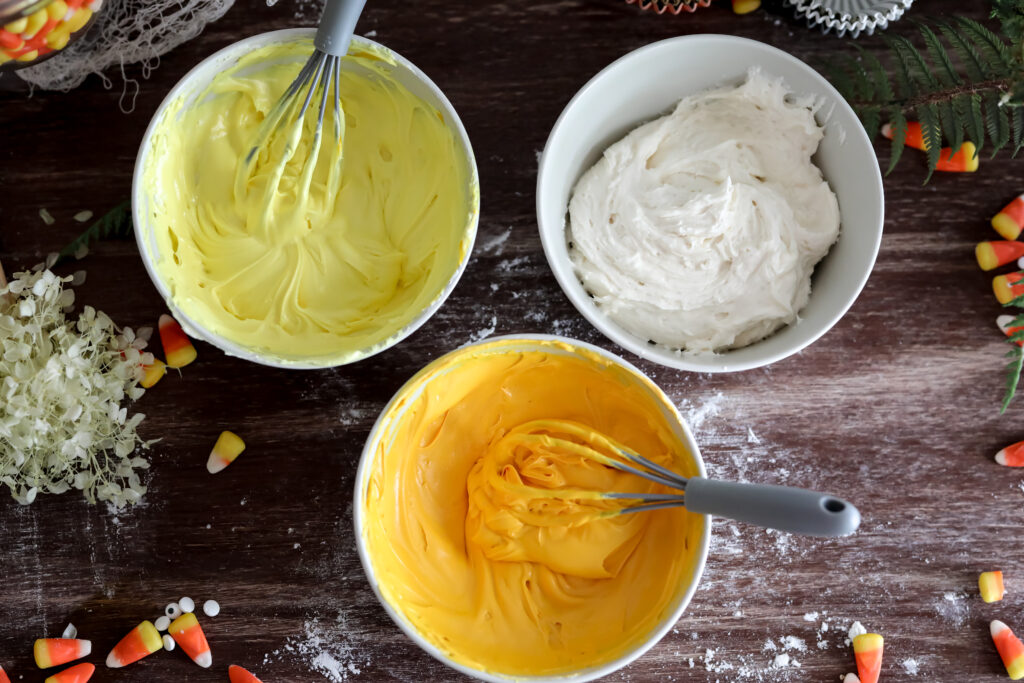 3 bowls of frosting one yellow one white one orange on a wood table