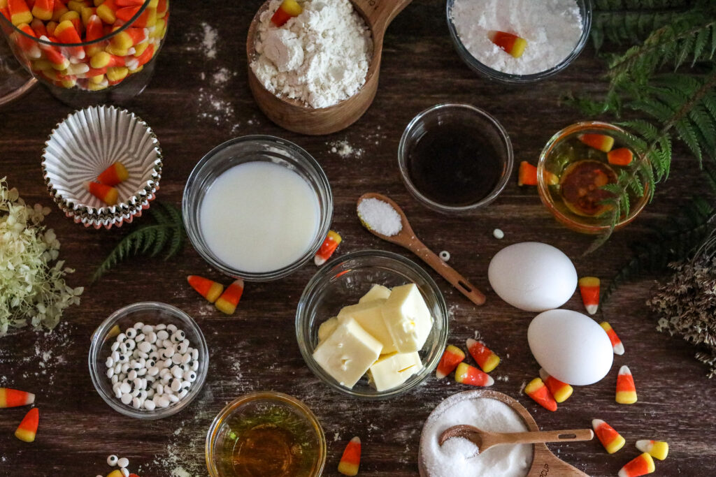 ingredients for gluten free Halloween cupcakes on a wood table with candy corns around it